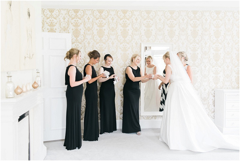 A bride in a Caroline Castigliano wedding dress and bridesmaids in floor length black dresses