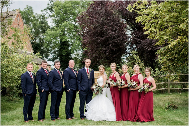 Bride in Essense of Australia and bridesmaids in red and ushers in navy at Blackwell Grange Cotswolds wedding venue