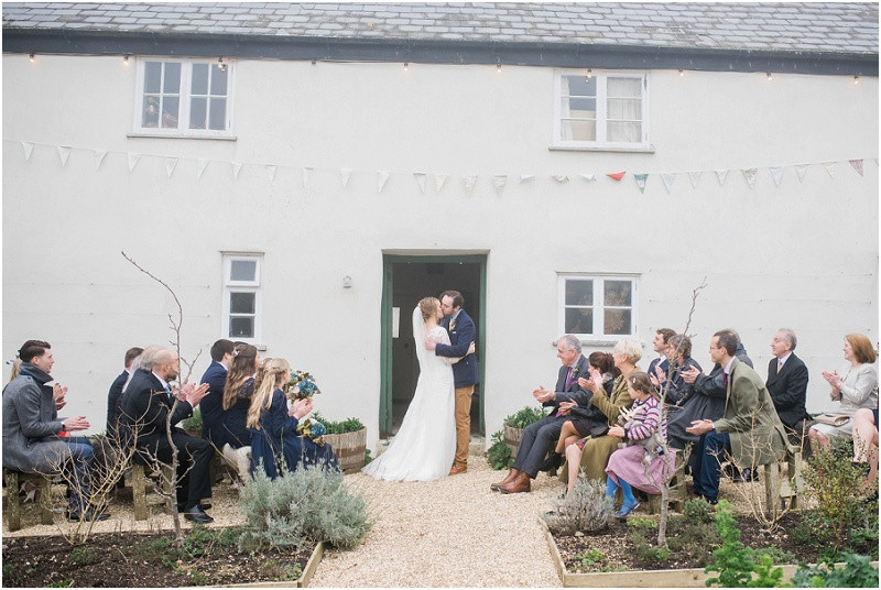 couple kiss after ceremony at boho wedding at River Cottage