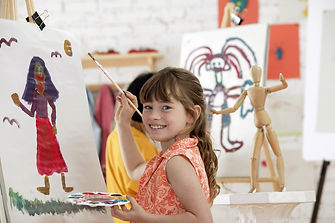 A little girl painting a picture that will need to be framed.