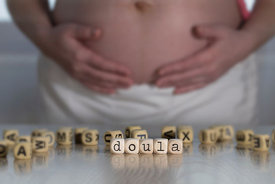 Word DOULA composed of wooden letters. P