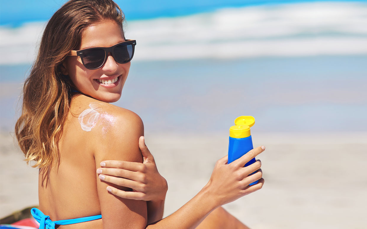 Woman-Applying-Sunscreen-On-Beach-FTR
