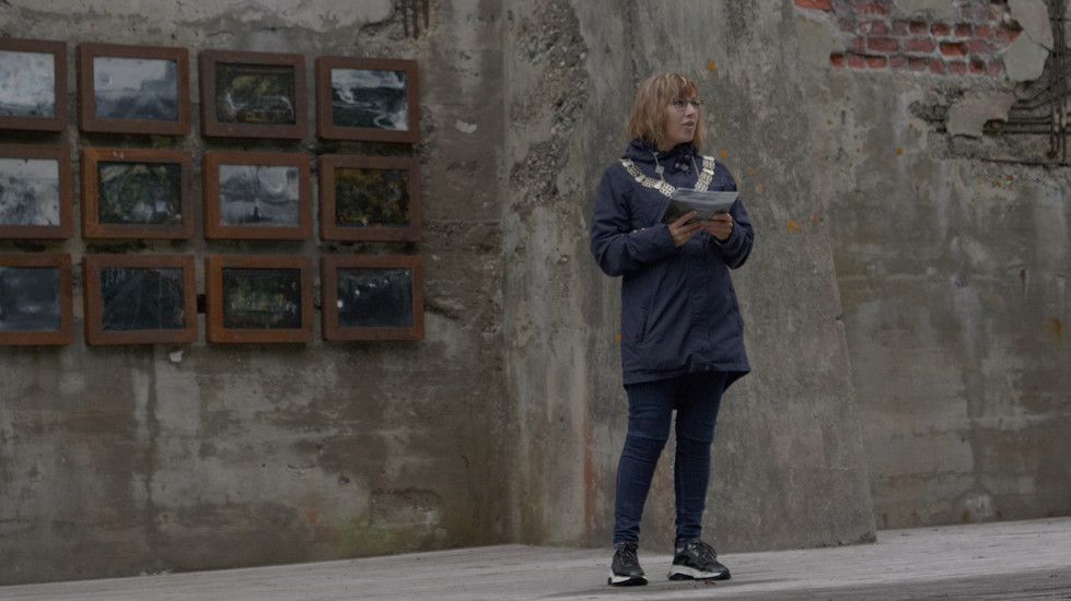 Ordførern Sigrun Prestbakmo åpner Salangen biennale. Verk i bakgrunn: Iren Gule - Forherding, 2017-2021, Olje, akryl, papir, voks, skjellakk og tegning på lerret i rustne jernrammer, 111 x 243 cm. Serie bestående av 15 bilder på 32 x 42 cm