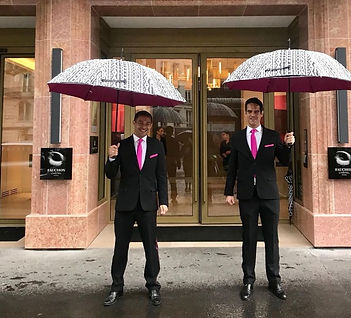 Two guys with umbrellas out front.jpg