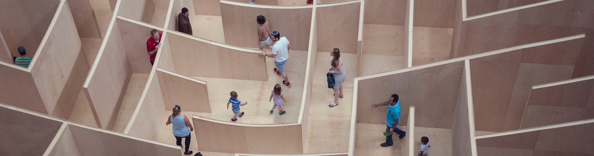 Families walking around a large wooden maze