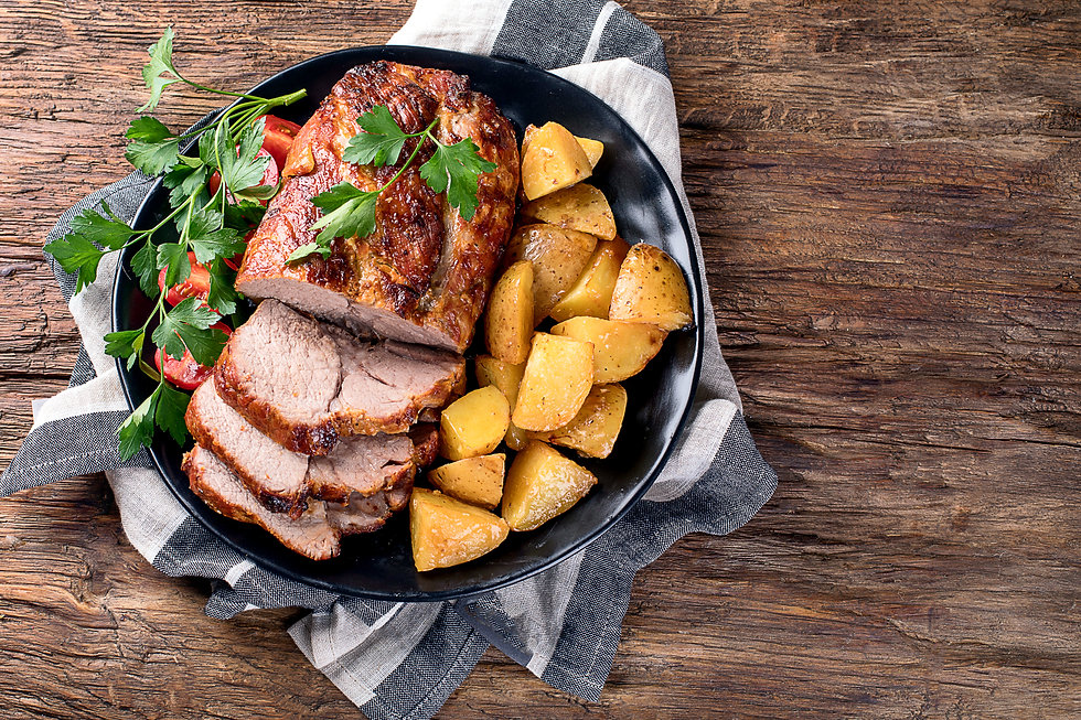 Roast pork with herbs and vegetables on rustic wooden table..jpg