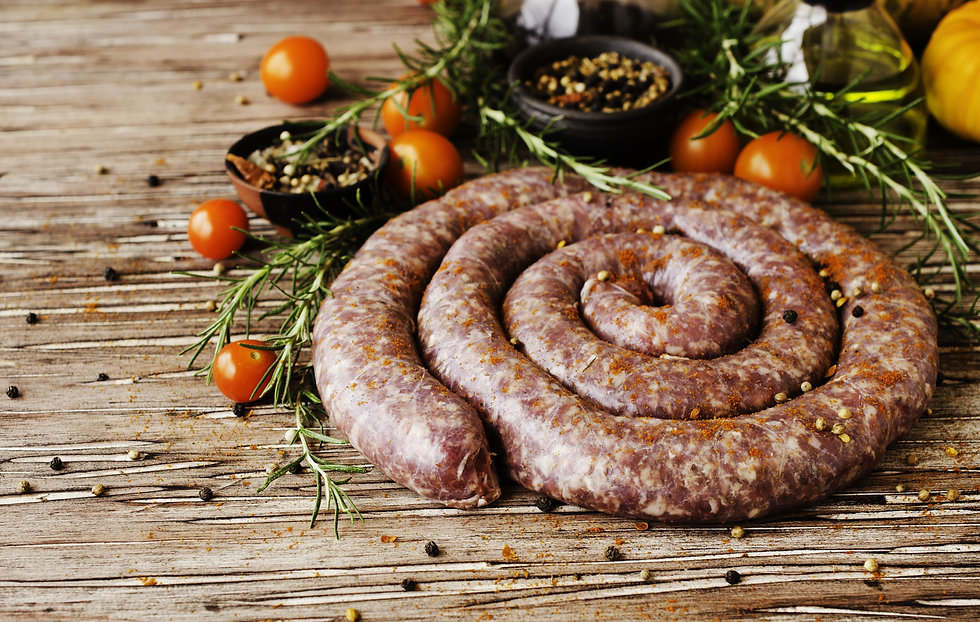 raw beef sausages with rosemary and spices on a wooden table, South African boerewors.jpg