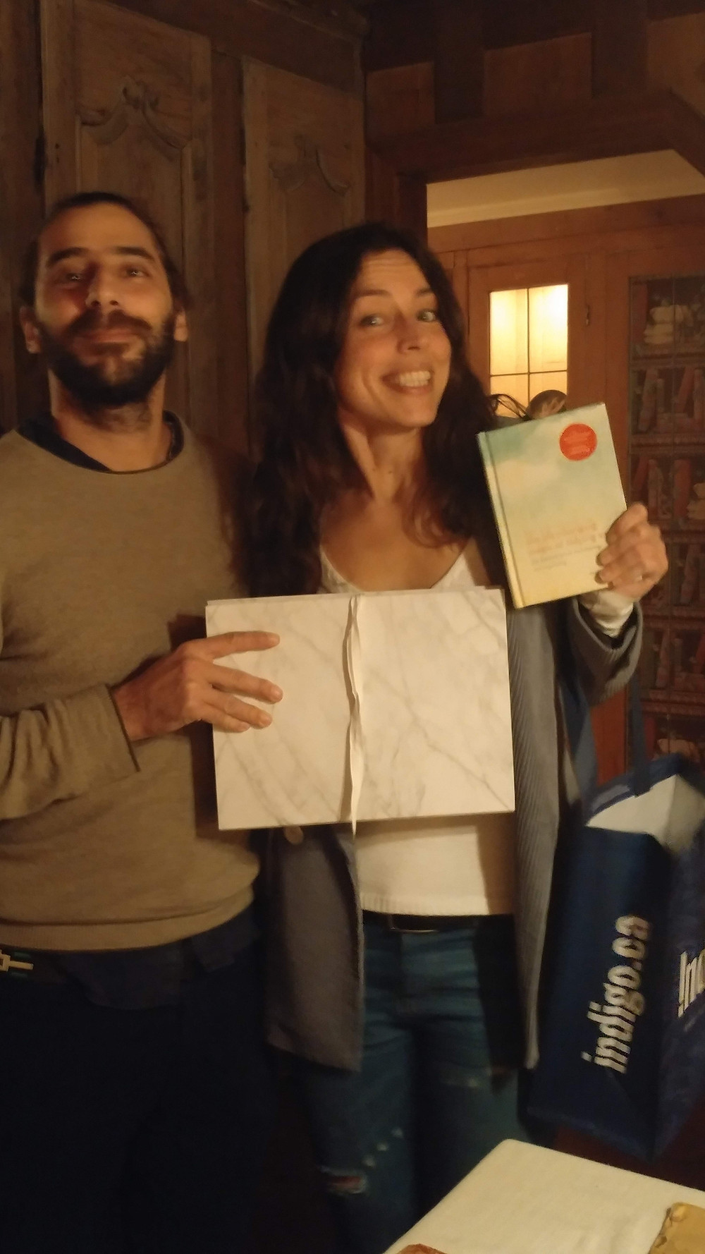 Couple holding a classifying folder and Marie Kondo book as Christmas gifts.