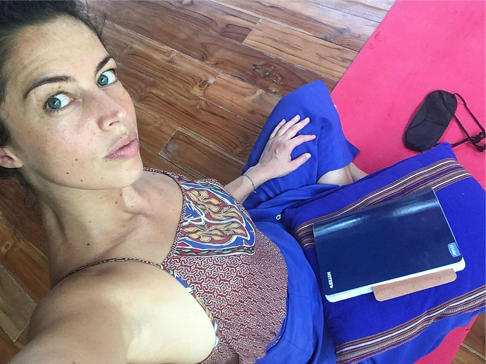 Natalie Vansier sitting in lotus position after meditation, with a notebook on her lap and an eye mask on the yoga mat in front of her.