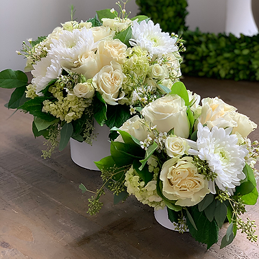 a large and a small flower arrangement with white roses and mums