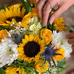 flower arrangement with sunflowers, yellow roses, thistle and white mums