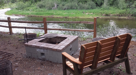 Ther River Cabin fire pit with bench and view of the Moyie River