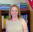 Assistant Principal Dorota Koczewska wearng a beige dress standing in front of a bookshelf loaded with books