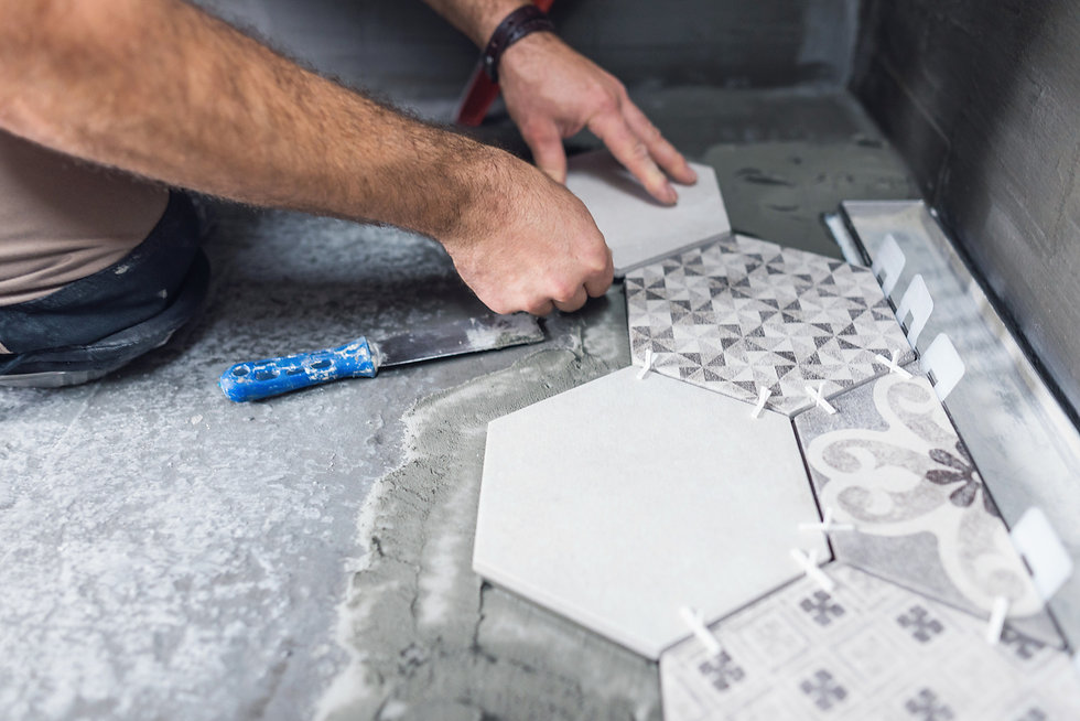 Hand laying patterned tiles onto a floor