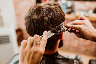 Man with long hair getting his hair cut with comb and scissors.jpg