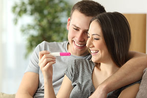 Happy couple checking pregnancy test sit