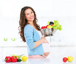 Pregnant Young Woman Cooking vegetables.
