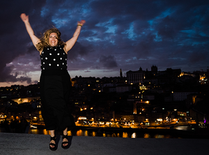 A woman jumping for joy over the scenery in Porto, Portugal.