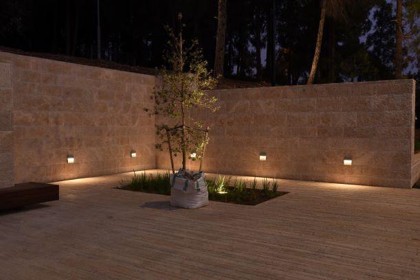 חצר פנימית. גופי תאורה שקועים בגדר האבן, מאירים לכיוון הרצפה