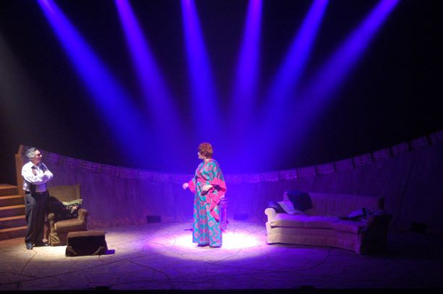 """אלומות אור ממורכזות לאמצע הבמה, רקע שחור עם כוכבים, והדגשים של אור בהיר על השחקנים. """"זהב טורקי"""" תיאטרון הקאמרי."""