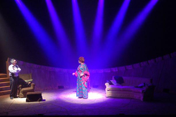 שחקנית במרכז, 6 אלומות אור כחולות עליה, עם נגיעות אור חם.