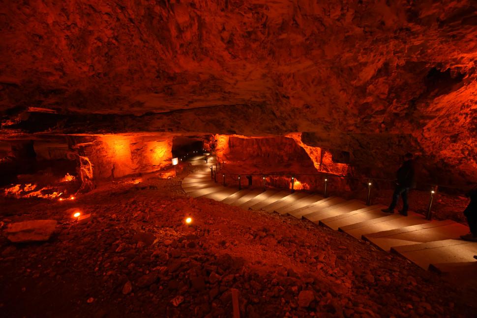 שביל הולכי הרגל בתוך מערת צדקיהו, מואר במרכז.  על קירות המערה בעומק גופי תאורה המדגישים את העוצמה והגודל של המערה..