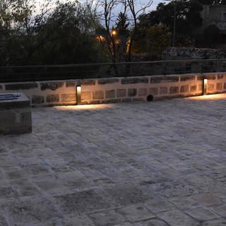 גופי תאורה על קיר האבן הנמוך, מאירים כלפי מטה