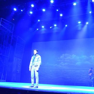 השחקן הראשי במרכ הבמה, אלומות אור כחולות מאחוריו.