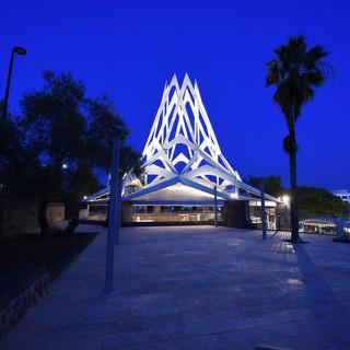 """מתחם קבר הרמב""""ם מרחוק. אלמנט המבנה מואר מבפנים, ונראה כמו להבת-אש בשמי הערב הכחולים"""