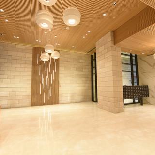 מבט צד על לובי הכניסה, גופי התאורה הגדולים מעל, רצפת שיש לבנה, ודגש של קיר קורות העץ והתאורה