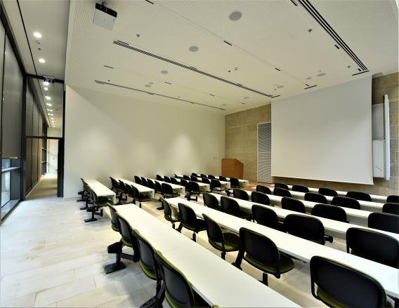 מבט מהצד על חדר הכיתה. גופי תאורה במרחקים סימטריים במסדרון. תאורה נסתרת בחלל החדר