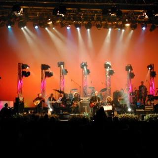 תמונת במה בגוונים של כתום, אדון וצהוב. אלומות אור למרכז הבמה.