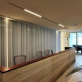 עמדת הקבלה של המשרד. פסי אור מהתקרה, ופסי אור על הקיר.