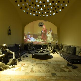 תצוגה של דמויות בחמאם, תאורה חמה וצהבהבה מלמעלה