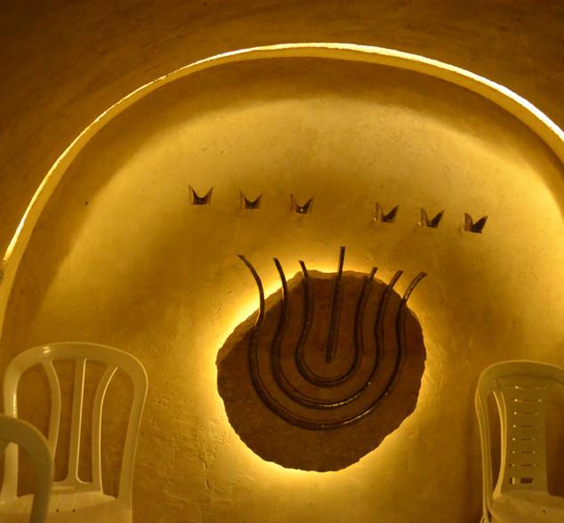 """הנקודה הקרובה ביותר אל """"קודש הקודשים"""" של בית המקדש. אלמנט עיצובי עגול המתכתב עם המנורה העתיקה, וגופי תאורה היוצרים עיגול אור עדין. נדמה שהמנורה מרחפת באוויר."""