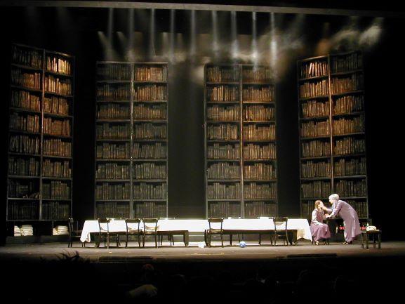 שתי שחקניות בימין, אלומות אור חדות כמו סכינים מלמעלה - מדגישות את השולחן הארוך והריק.