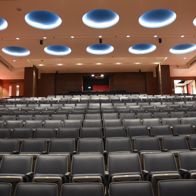 אודיטוריום מרווח, כיסאות אפורים, ומעל גופי תאורה שקועים בתקרה, מוארים באור בלתי-ישיר, ויוצרים טבעות של אור