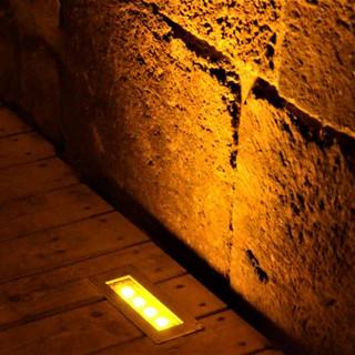 תמונת תקריב על גוף תאורה LED שקוע-רצפה, אשר מאיר את קיר האבנים