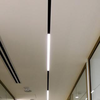 תקריב של גופי התאורה במסדרון. מרווחים סימטריים היוצרים תבנית וקצב לאור