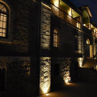 מבט מהצד על קיר המבנה הקדמי. פסי אור במרחקים שווים, מדגישים את הקיר, ונותנים מקצב לאור.