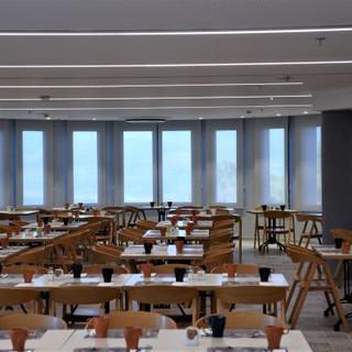 חדר האוכל המרכזי. פסי תאורה סימטריים שקועים בתקרה, ותאורת ספוטים ליד החלונות