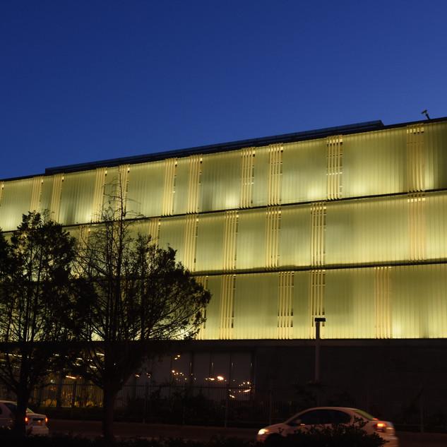 הבנין מואר בגופי תאורה נסתרים, בין תריסי הבטון, מכיוון הבניין החוצה.
