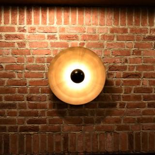 גוף תאורה מעוצב ייחודי, המדגיש את קיר הלבנים האדומות