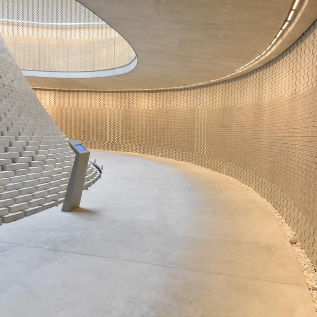 קיר השמות האינסופי, מואר מלמעלה באור בלתי ישיר. משמאל חלק מהקונסטרוקציה הייחודית של הלבנים המטפסות מעלה לשמיים. מעל - קרני אור - תאורה טבעית הנכנסים למבנה.