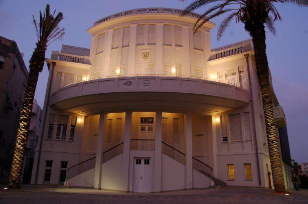 אור רך על מרפסת בניין העירייה וגופי תאורה תקופתיים מעל גרם המדרגות