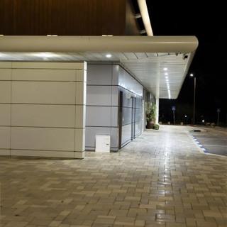 הקו העליון של המבנה מודגש באור. ניתן לקראות את המרכז המסרחי מהכביש הראשי