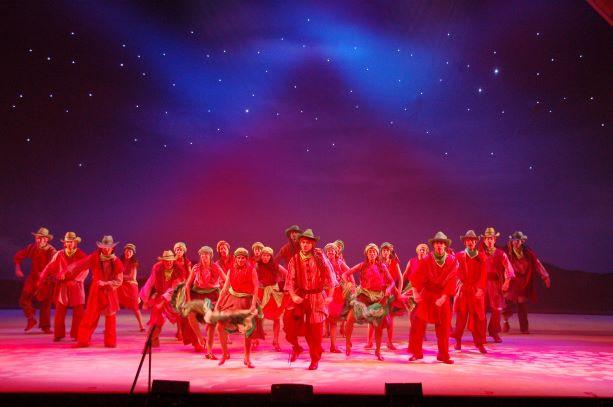 קאסט הרקדנים בתמונת במה בגוונים של אדום בקדמת הבמה, וכחול בגב הבמה