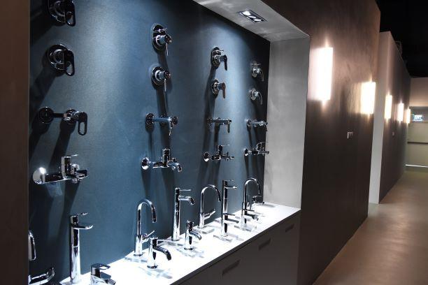 קיר של ברזים למטבח, מוארים באור-עילי הגורם להם להיראות כיצירת אומנות