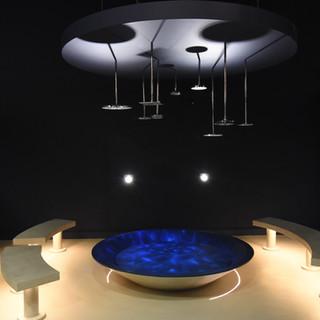 פינת ישיבה מעגלית, ספסלי שיש, שולחן כחול, ותאורה עילית ייחודית הגורמת למקום להיראות כמו פסל סביבתי