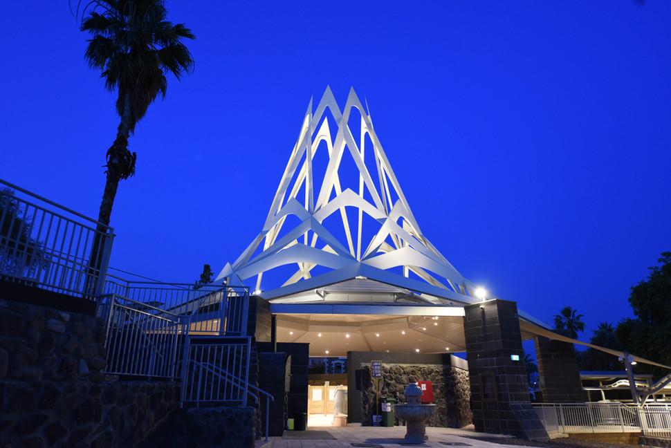"""קבר הרמב""""ם בטבריה. פסל להבת-האש על הגג מואר באור בלתי ישיר, ומדגיש את קווי המתאר שלה."""